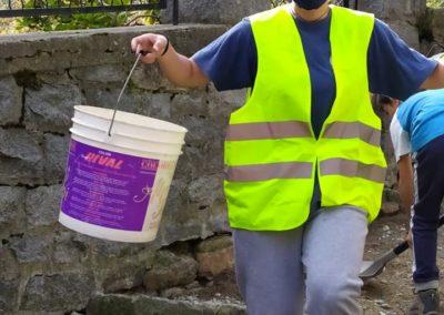 Volontaria impegnata nella pulizia di una scalinata in pietra distrutta dall'alluvione