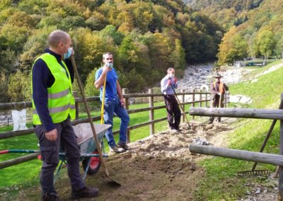 I volontari raccolgono il fango portato dall'alluvione nella zona picnic